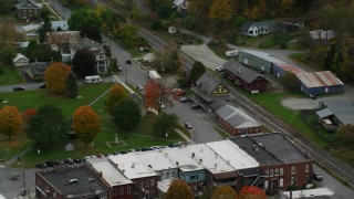 AX150_445 - 6K stock footage aerial video orbiting railroad tracks and station, town square, small town, autumn, South Royalton, Vermont