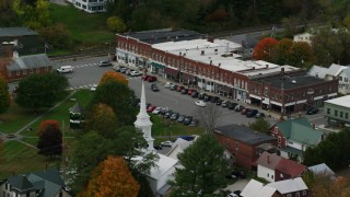 AX150_447 - 6K stock footage aerial video orbiting a row of shops near town square, small rural town, autumn, South Royalton, Vermont