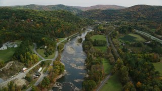 AX150_451 - 6K stock footage aerial video flying over White River, roads, approaching small bridge, autumn, South Royalton, Vermont