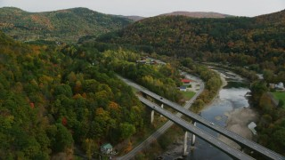 AX150_452 - 6K stock footage aerial video flying over White River, approach Interstate 89, small bridge, pan left, autumn, South Royalton, Vermont