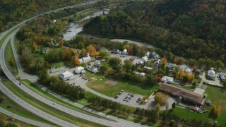 AX150_455 - 6K stock footage aerial video orbiting a small rural town, colorful foliage in autumn, Sharon, Vermont