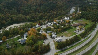 AX150_456 - 6K stock footage aerial video orbiting a small rural town near the White River, autumn, Sharon, Vermont