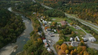 AX150_457 - 6K stock footage aerial video orbiting a small rural town on the White River, autumn, Sharon, Vermont