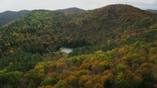 AX150_458 - 6K stock footage aerial video tilting down over pond, brightly colored forested hills in autumn, Sharon, Vermont