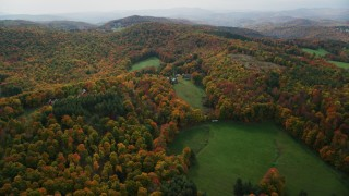 AX150_460 - 6K stock footage aerial video flying over colorful forest, hills, approach rural home, tilt down, autumn, North Pomfret, Vermont