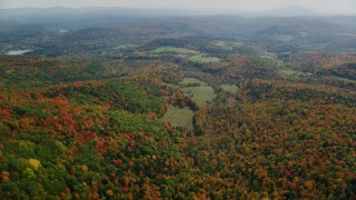 AX150_464 - 6K stock footage aerial video flying over brightly colored forest, approaching a farm, autumn, Quechee, Vermont