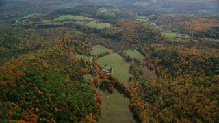 AX150_465 - 6K stock footage aerial video flying over grassy clearing, colorful forest, approach farm, Quechee, Vermont