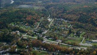 AX150_468 - 6K stock footage aerial video flying by a small rural town, colorful foliage, autumn, cloudy, Quechee, Vermont