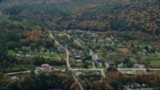 AX150_469 - 6K stock footage aerial video flying by small rural town, colorful trees, autumn, cloudy, Quechee, Vermont