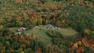 AX150_470 - 6K stock footage aerial video flying by small farm, grassy clearings and colorful trees, autumn, Quechee, Vermont