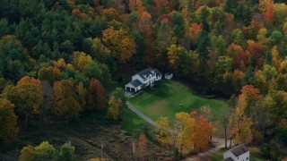 AX150_471 - 6K stock footage aerial video flying by rural homes, lawns, brightly colored trees in autumn, Quechee, Vermont