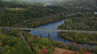 AX150_474 - 6K stock footage aerial video flying by Interstate 89, small bridge, Connecticut River, autumn, Lebanon, New Hampshire