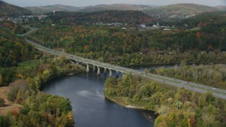 AX150_475 - 6K stock footage aerial video of Interstate 89, small bridge spanning Connecticut River, autumn, Lebanon, New Hampshire