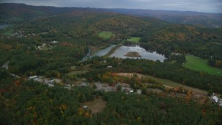 AX151_005 - 6K stock footage aerial video flying by Dewey's Pond, rural homes, autumn, overcast, Quechee, Vermont