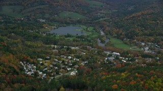 AX151_006 - 6K stock footage aerial video flying by Lake Pinneo, nearby rural neighborhood, autumn, Quechee, Vermont