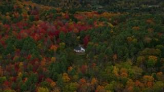 AX151_007 - 6K stock footage aerial video flying by rural home, dense colorful trees, tilt down, autumn, Quechee, Vermont