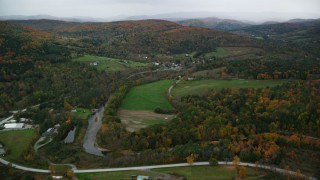 AX151_008 - 6K stock footage aerial video flying over Woodstock Road, approach a small rural town, autumn, Taftsville, Vermont