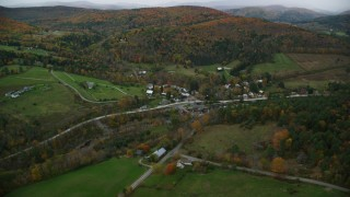 AX151_009 - 6K stock footage aerial video approaching small rural town, tilt down over bridge spanning Ottauquechee River, autumn, Taftsville, Vermont