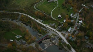 AX151_010 - 6K stock footage aerial video of a bird's eye view flying away from bridge, Ottauquechee River, small town, autumn, Taftsville, Vermont