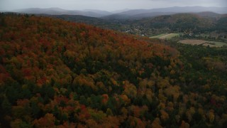 AX151_011 - 6K stock footage aerial video flying over forest, Blake Hill, reveal, small rural town, autumn, Woodstock, Vermont