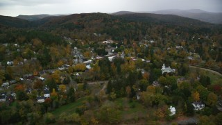 AX151_014 - 6K stock footage aerial video flying by Ottauquechee River, small rural town, overcast, autumn, Woodstock, Vermont