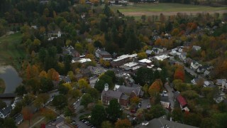 AX151_017 - 6K stock footage aerial video orbiting small rural town with colorful foliage in autumn, Woodstock, Vermont