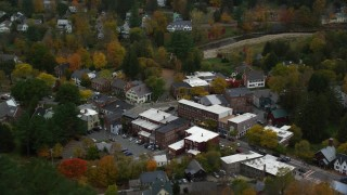 AX151_018 - 6K stock footage aerial video orbiting small rural town, brightly colored trees in autumn, Woodstock, Vermont
