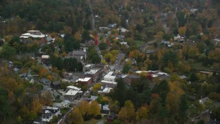 AX151_019 - 6K stock footage aerial video orbiting small rural town, shops, autumn, overcast, Woodstock, Vermont