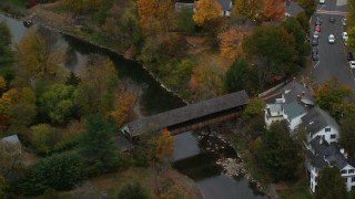 AX151_021 - 6K stock footage aerial video orbiting a covered bridge, Ottauquechee River, autumn, Woodstock, Vermont