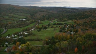 AX151_023 - 6K stock footage aerial video flying over rural homes, grassy clearings, colorful foliage, autumn, Woodstock, Vermont