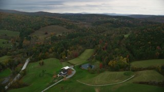 AX151_024 - 6K stock footage aerial video flying over rural homes, approaching colorful forests, hills, autumn, Woodstock, Vermont