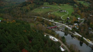 AX151_027 - 6K stock footage aerial video flying by small covered bridge, Ottauquechee River, small rural town, autumn, Taftsville, Vermont