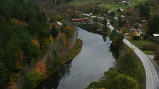 AX151_031 - 6K stock footage aerial video flying over Ottauquechee River, approach covered bridge, small rural town, autumn, Taftsville, Vermont