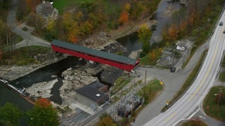 AX151_032 - 6K stock footage aerial video flying by covered bridge, Ottauquechee River, tilt down, autumn, Taftsville, Vermont