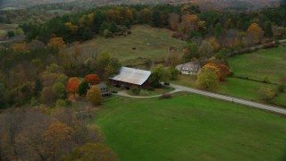 AX151_033 - 6K stock footage aerial video orbiting small farm, barn, grass clearings, colorful foliage in autumn, Taftsville, Vermont