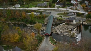 AX151_035 - 6K stock footage aerial video approaching small rural town, reveal covered bridge, Ottauqueche River, autumn, Taftsville, Vermont