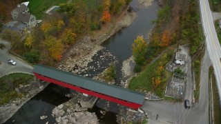 AX151_036 - 6K stock footage aerial video of a bird's eye view over covered bridge, Ottauquechee River, autumn, Taftsville, Vermont