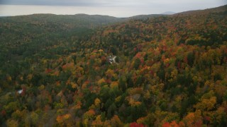 AX151_037 - 6K stock footage aerial video flying over brightly colored forested hills, approach rural homes, autumn, Taftsville, Vermont