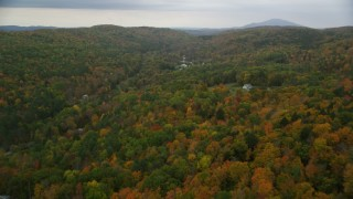 AX151_039 - 6K stock footage aerial video flying over forested hills, approaching rural homes, autumn, overcast, Hartland, Vermont