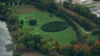 AX151_047 - Aerial stock footage of Flying by a hedge maze in a park, trees and colorful foliage, autumn, Hartland, Vermont