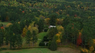 AX151_051 - 6K stock footage aerial video flying by colorful trees, revealing isolated mansion, autumn, Cornish, New Hampshire