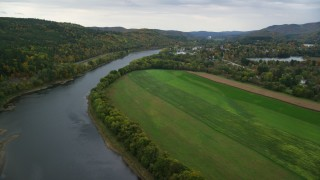 AX151_055 - 6K stock footage aerial video flying over Connecticut River, approaching small town, autumn, Windsor, Vermont