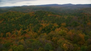 AX151_065 - 6K stock footage aerial video flying over colorful forest, hills, revealing farms, autumn, Cornish, New Hampshire