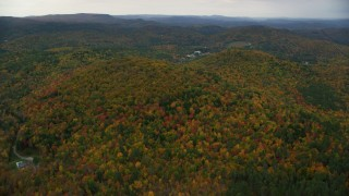 AX151_067 - 6K stock footage aerial video flying by brightly colored forested hills, autumn, overcast, Cornish, New Hampshire