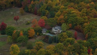 AX151_068 - 6K stock footage aerial video flying away from isolated homes, brightly colored trees, autumn, Cornish, New Hampshire