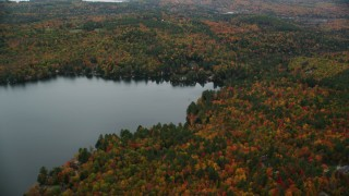 AX151_077 - 6K stock footage aerial video approaching waterfront homes, Perkins Pond, forest, autumn, Sunapee, New Hampshire