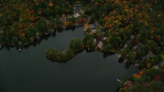 AX151_078 - 6K stock footage aerial video of a bird's eye view over Perkins Pond, homes, colorful forest, autumn, Sunapee, New Hampshire
