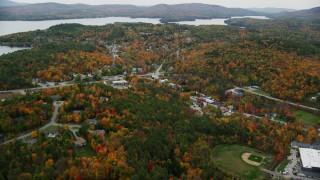 AX151_079 - 6K stock footage aerial video flying over colorful trees, small rural town, tilt down, autumn, Sunapee, New Hampshire