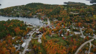 AX151_080 - 6K stock footage aerial video flying over small rural town, pan to Sunapee Harbor, autumn, Sunapee, New Hampshire