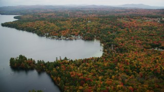 AX151_085 - 6K stock footage aerial video flying by waterfront homes, colorful forest, Lake Sunapee, autumn, Newbury, New Hampshire